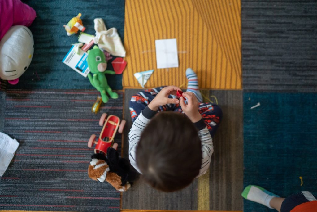 top-view-photography-of-toddler-playing-with-toy-2790771